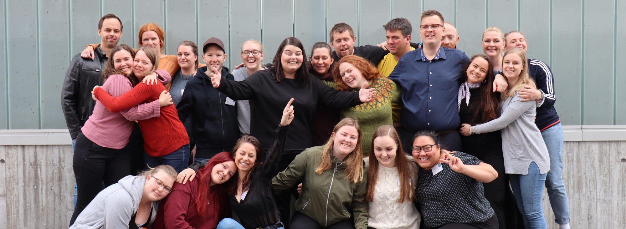 Medlemmer i Ung Kreft står samlet, holder rundt hverandre og smiler inn i kamera